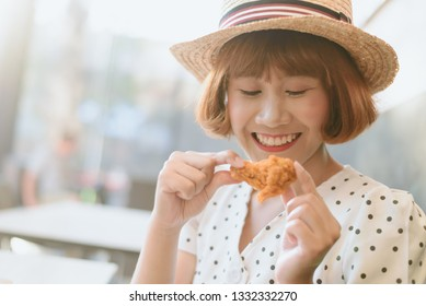 Attractive Asian woman eating fried chicken.