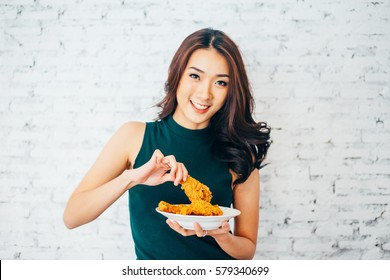 Attractive Asian woman eating fried chicken drumstick over white brick background