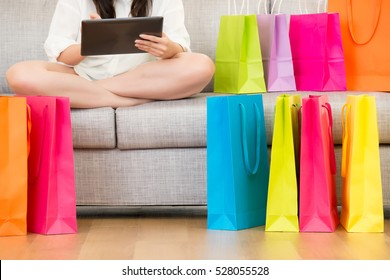 attractive asian woman enjoy online shopping with digital tablet sitting on sofa colorful shopping bags around. indoor living room background