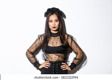 Attractive asian woman in halloween costume looking disappointed and skeptical. Female in black lace dress and wreath looking arrogant, trick or treat in witch outfit, standing white background