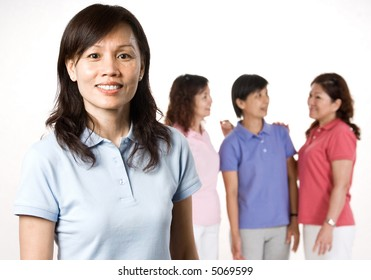 An attractive Asian woman in her 40s standing with a group of friends talking behind her