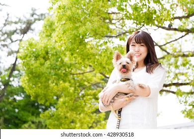 attractive asian woman holding dog in the park
