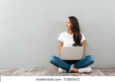 Attractive asian woman holding laptop computer while sitting on the floor with legs crossed and looking away at copy space isolated over gray background
