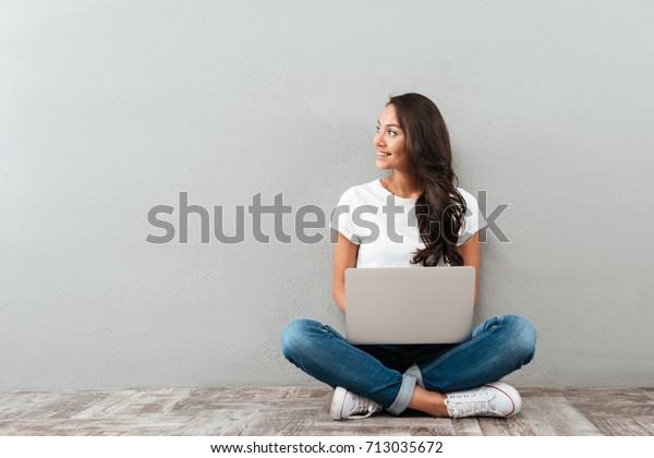 Attraktive asiatische Frau, die einen Laptop hält, während sie auf dem Boden sitzt, die Beine gekreuzt und Kopienraum einzeln auf grauem Hintergrund betrachtet