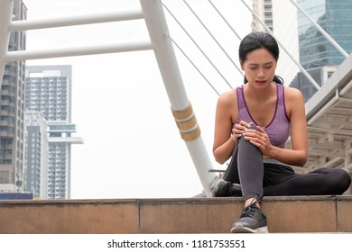 Attractive Asian woman injured her ankle during doing exercise. Sport accident concept.
