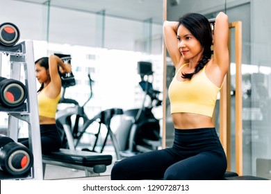 Attractive Asian woman lifting a dumbbell with dumbbell row at gym