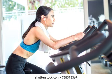 Attractive Asian Woman on exercise bikes at a gym. Woman exercise  Concept.