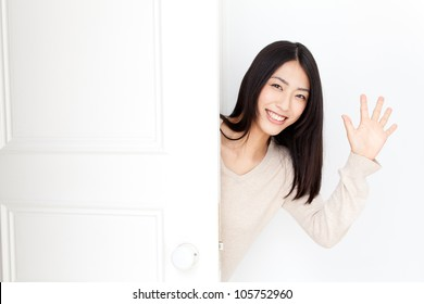 attractive asian woman opening door