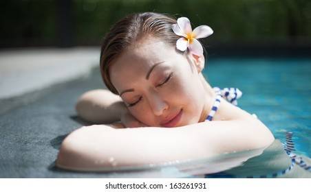 Attractive Asian Woman in Pool having a rest on the side