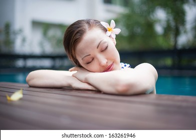 Attractive Asian Woman in Pool resting and enjoying on pool deck