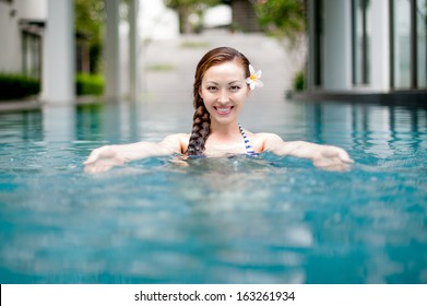Attractive Asian Woman in Pool welcoming with a smile