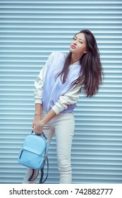 Attractive asian woman portrait with elegant hairstyle and perfect soft colorful makeup. Gorgeous models face with yellow pink make-up in casual sporty clothes and bagpack. Fashion shot outdoors