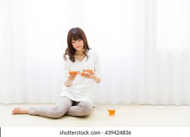 attractive asian woman reading book in the living room