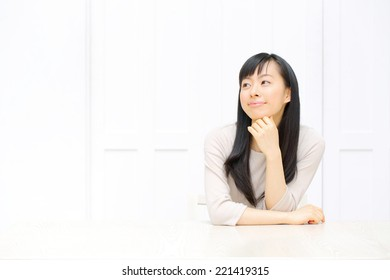 attractive asian woman relaxing in the all white room