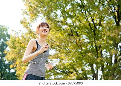 attractive asian woman running in the park
