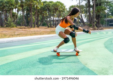 Attractive Asian woman with safety skateboarding knee pad skating at skateboard park by the beach. Happy female enjoy summer outdoor active lifestyle play extreme sport surf skate at public park.