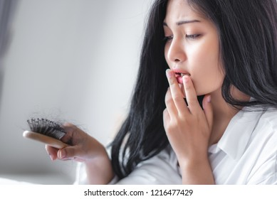Attractive Asian woman serious about her brush for presentation hair loss problem and looking at comb