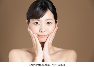 attractive asian woman skin care image on brown background