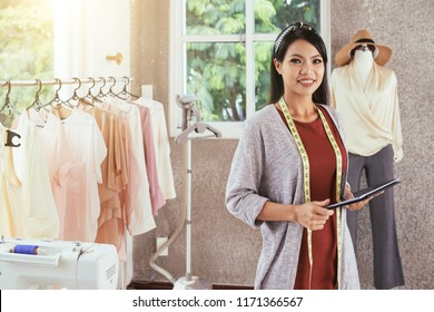 Attractive Asian woman smiling and looking at camera while holding modern tablet and standing in stylish tailoring workshop