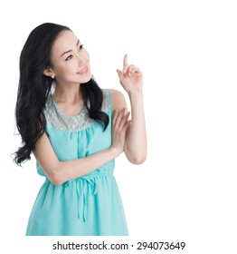 Attractive Asian woman smiling and pointing at the side
