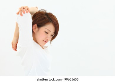 attractive asian woman stretching in studio
