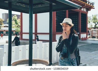 Attractive asian woman traveler experience japanese religion culture praying at Shinto shrine in osaka japan. young girl backpacker eye closed peaceful with blessing hands together in shinnoji temple