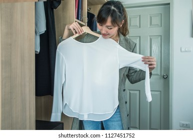 Attractive Asian  woman trying white shirt in front of mirror in closet door at home .