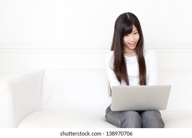 attractive asian woman using laptop on the sofa