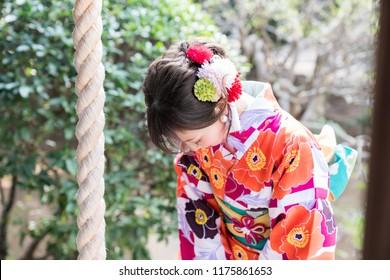 Attractive asian woman wearing japanese kimono praying at a Shinto shrine.
