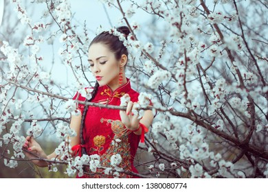 Attractive asian woman wearing kimono standing in blossoming garden. Gorgeous creative portrait outdoor on the nature.