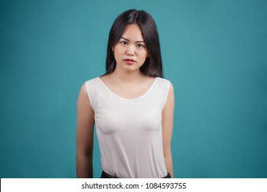 Attractive asian woman in white transparent top looking at camera isolated on blue background