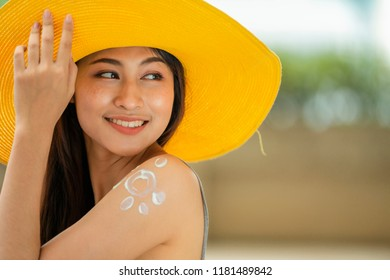 Attractive asian woman in yellow hat with healthy skin applying sunscreen standing outdoors on a sunny day.