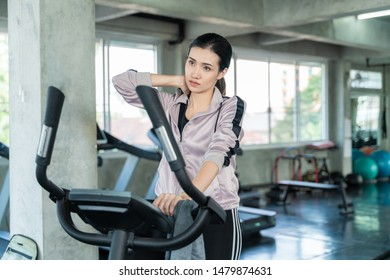 Attractive asian women be tired after cycling in fitness gym, Healthy lifestyle