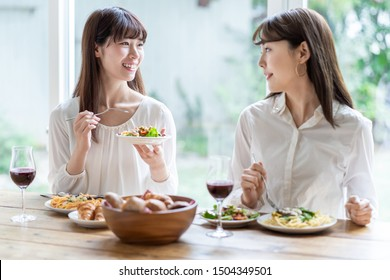 attractive asian women enjoying lunch in living room