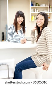 attractive asian women relaxing in the kitchen