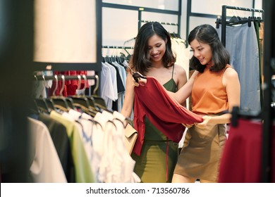 Attractive Asian women shopping for clothes on sale