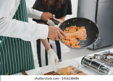Attractive asian young man cooking food in the nice kitchen for dinner