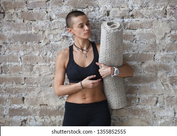 attractive athletic short hair caucasian woman in sportswear with yoga mat