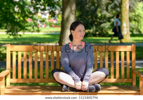 Attractive athletic supple woman sitting cross legged on a wooden park bench under leafy green trees smiling happily as she looks to the side