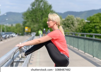 Attractive athletic woman doing warming up exercises using the railing on a pedestrian bridge as she prepares for her daily jog and workout
