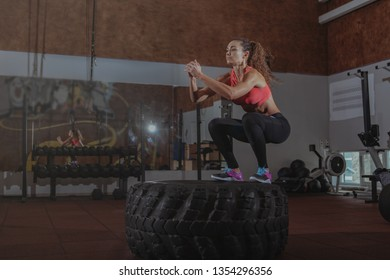 Attractive athletic woman jumping on a huge tire at, copy space. Energetic female athlete working out at the gym, jumping high on a big wheel