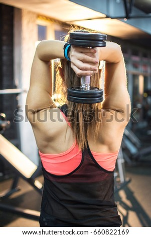 Attractive athletic woman pumping up muscles with dumbbell, back view.