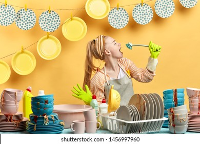 attractive awesome girl in gray apron using brush as a microphone in the kitchen with modern interior. plates are hanging on the clothespins