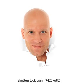Attractive bald man breaks his head trough white paper wall. All on white background.