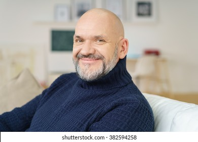 Attractive bald middle-aged man with a goatee sitting relaxing on a couch at home looking at the camera with a lovely wide engaging smile