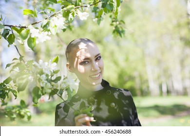 Attractive bald sexy woman walking in forest. Outdoors lifestyle portrait of pretty girl