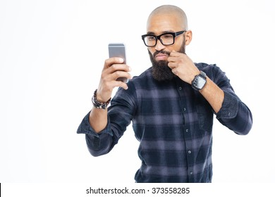 Attractive baldheaded african american man in glasses touching moustache and taking selfie