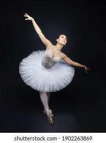 attractive ballerina poses gracefully in the studio on a black background