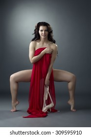 Attractive ballet dancer posing with red cloth