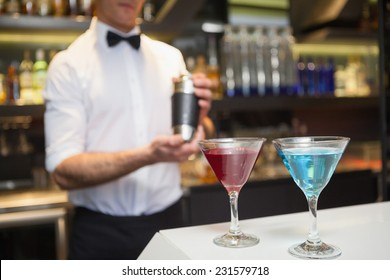 Attractive bar man making a cocktail in a bar